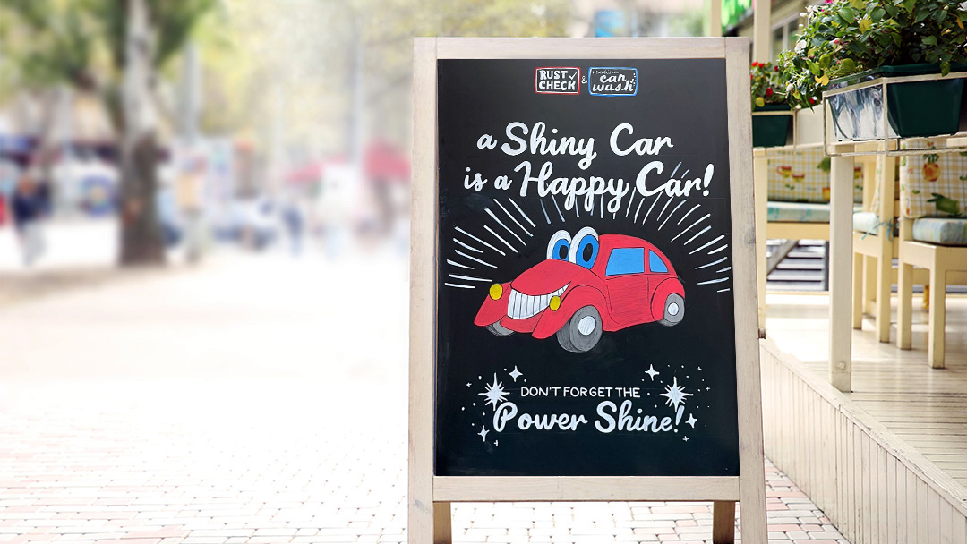 a chalkboard a-frame with a car wash image